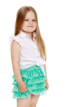 짧은 녹색 치마에서 어깨 아래 긴 금발 머리와 백인 소녀. 어린 소녀는 옆으로 카메라쪽으로 향했다. 근접 - 흰색 배경에 격리 됨