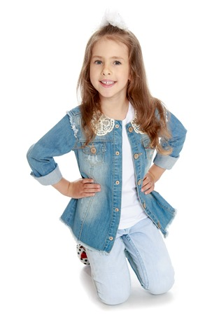 sweetly: Nice little girl in denim suit. The girl kneeling on the floor. She smiles sweetly at the camera - Isolated on white background Stock Photo