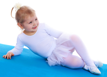 Cute little gymnast in White tracksuit lying on the Mat sports-Isolated on white background
