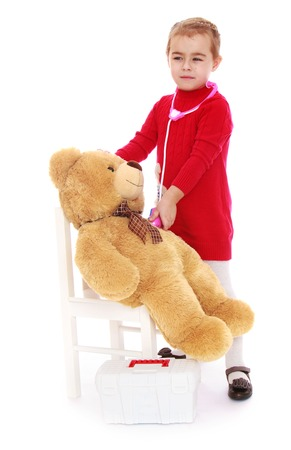 playing with spoon: Gentle little girl playing doctor with Teddy bear - Isolated on white background