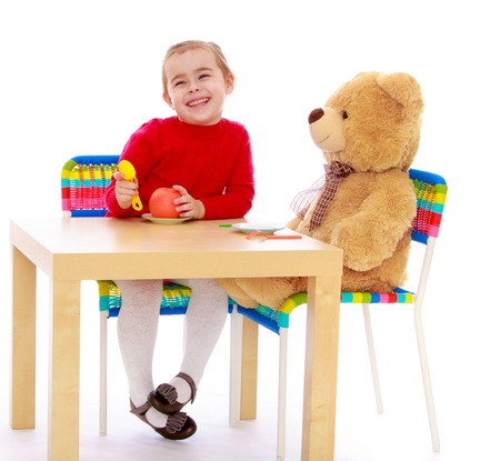 playing with spoon: Cute little girl in a red dress in a Montessori kindergarten. Girl sitting at the table with a large Teddy bear and feeds him an Apple - Isolated on white background