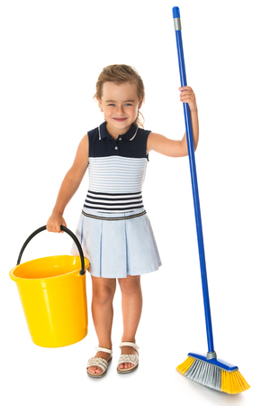 tidying up: Diligent little girl is tidying up the apartment. In the hands of the girl holding a brush and bucket - Isolated on white background Stock Photo