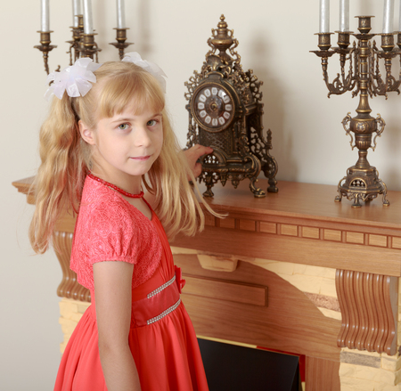 mantelpiece: Beautiful little girl in a red dress staring at the clock standing on the mantelpiece