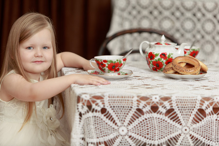 chubby girl: Cute little chubby girl with long, blonde hair below the shoulders is sitting at the table. The girl is now drinking tea