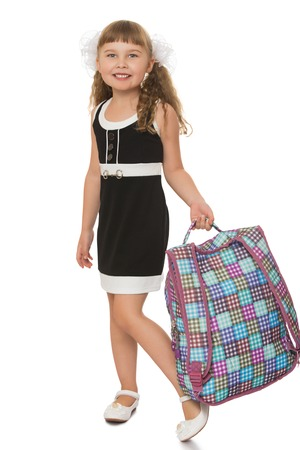 satchel: Laughing girl in the black school dress . The girl carries a satchel- Isolated on white background