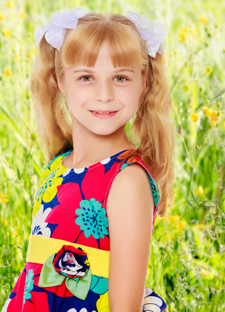 tied girl: Sweet, adorable little girl with long blonde ponytails on her head tied with white bows. Close-up.On the background of green grass and yellow wild flowers, blurring the background. Stock Photo