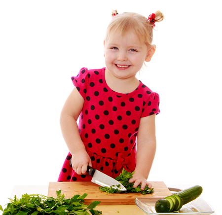girl with knife: Cheerful little girl standing at the kitchen table. The girl with a knife cuts the cucumber-Isolated on white background