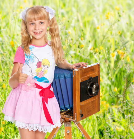 well head: Beautiful little girl with long blonde ponytails on the head posing with an old camera. The girl held out her hands raised in the Upper thumb . Gesture all is well. Stock Photo