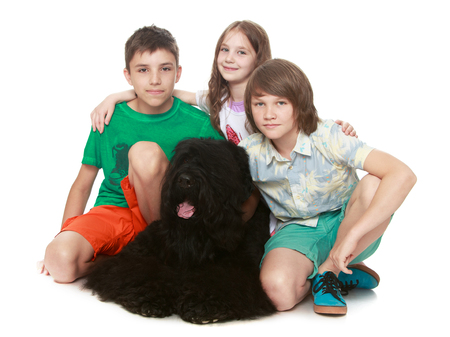 Two teenager boy and cute little girl hugging a big black dog - Isolated on white background