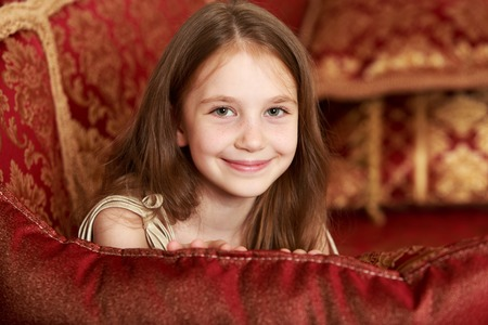 niños rubios: Gentle little girl with long brown hair to her waist . Girl lying on a luxurious cushion Arabian sofa Foto de archivo
