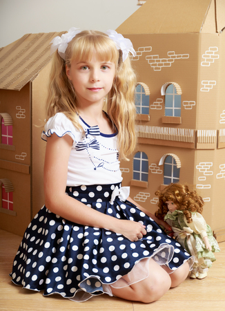 ponytails: Cute little girl blonde with long ponytails on her head , playing with a doll from a cardboard small house Stock Photo