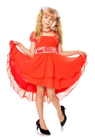 Fashionable little girl with long, blonde ponytails on her head in a bright orange dress . Feet girl high-heeled shoes.-Isolated on white background Stock Photo