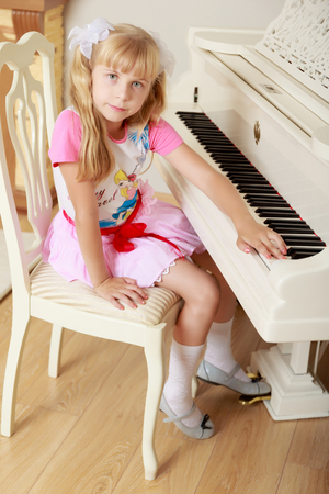 Cute little blonde girl sitting next to the piano facing away from the tool