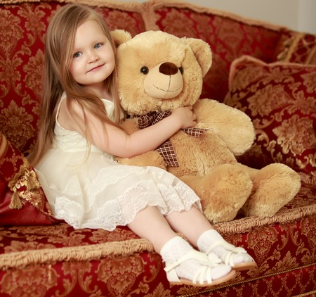 Adorable little round-faced girl with long, blonde hair below the shoulders, little Princess in a white dress. Girl hugging Teddy bear Stock Photo