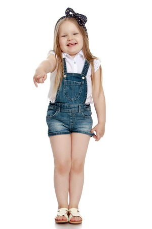 chubby girl: Funny little chubby girl in short denim jumpsuit. Girl laughing pointing in the direction - Isolated on white background