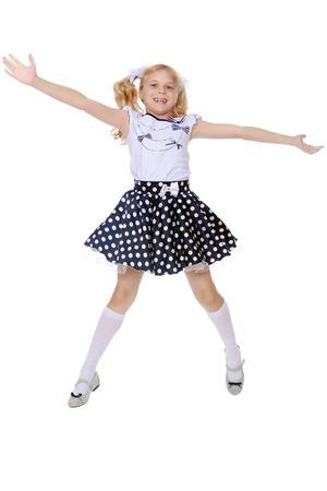 Glückliches kleines Mädchen in der kurzen gepunkteten Kleid springt, weit gespreizt seine Arme und Beine-isoliert auf weißem Hintergrund