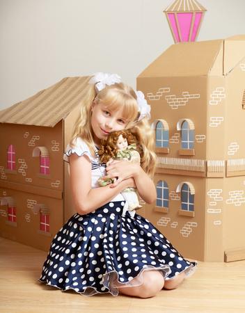 Bella bambina con lunghe code di cavallo bionda in testa, giocando con una bambola in prossimità di una casa di cartone Archivio Fotografico
