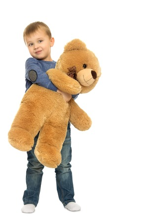 hugged: Small blonde boy hugged the big Teddy bear - Isolated on white background