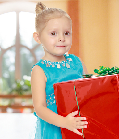 shool: Caucasian little girl in a blue dress, holding the hands of the big red box that is a gift.Girl holding a box in front of him.