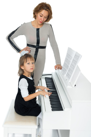 musical notation: Diligent little girl at a music school teaching musical notation. Beside her is her teacher - Isolated on white background