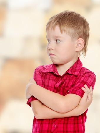 Nadenkend jongetje in het rode shirt, leg mijn handen op zijn borst. Detailopname. Stockfoto