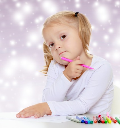 shool: Pretty little blonde girl drawing with markers at the table.The girl thoughtfully looks into the camera.The concept of celebrating the New year, Holy Christmas, or childs birthday on a purple background and white snowflakes.