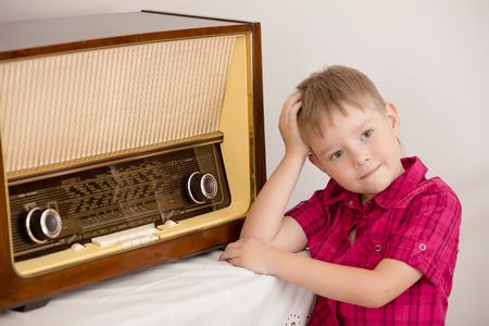 Style rétro, entouré de vieilles choses années cinquante du siècle dernier. Mignon petit garçon blond en chemise rouge pose près de la vieille radio. Banque d'images