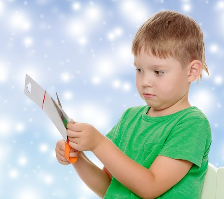 shool: Cute little boy in the green shirt without a pattern , cut the cardboard with scissors.The concept of celebrating the New year, Holy Christmas, or childs birthday on a blue background and white snowflakes.