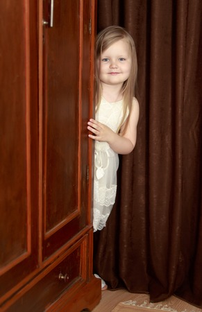 Lovely little round-faced girl with long, blonde hair below the shoulders, in a white dress. The girl peeks out from behind the vintage wardrobe