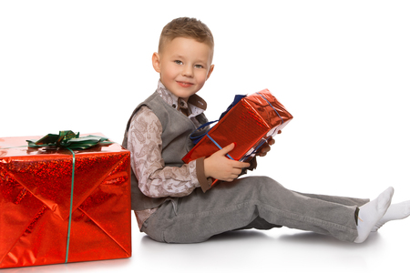 Beautiful little boy in gray a new costume, holding a box with a gift . the boy sits on the floor. Turning the camera sideways - Isolated on white background Stock Photo