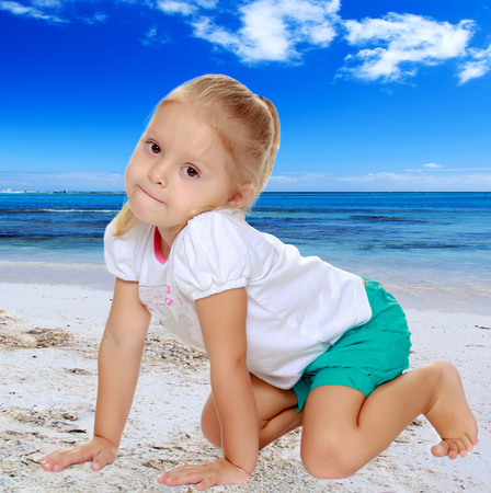 shool: The concept of family happiness and children in the summer on the sea among palm trees.Cute little blond girl in white tank top without a pattern.The girl is on all fours. Stock Photo