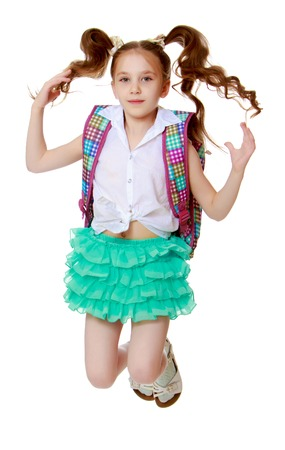 Joyful little girl with long hair to the waist which wire braided white ribbons. In a white shirt without a pattern and green short skirt. Girl jumping with legs tucked under . Stock Photo