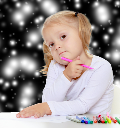 plaything: Pretty little blonde girl drawing with markers at the table.The girl thoughtfully looks into the camera.