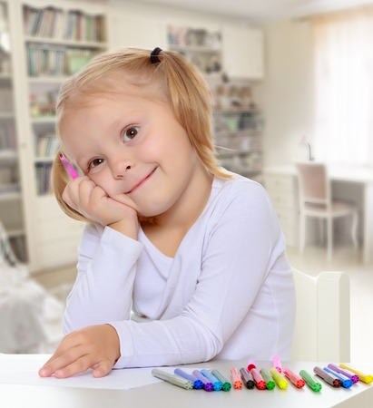 shool: The concept of family happiness,and preschool education of the child , against a childs room with bookshelves.Pretty little blonde girl drawing with markers at the table.Girl put head on his hand Stock Photo