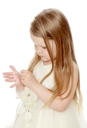 Adorable little round-faced girl with long, blonde hair below the shoulders, in a white dress. The girl looks at his hand. Close-up - Isolated on white background Stock Photo