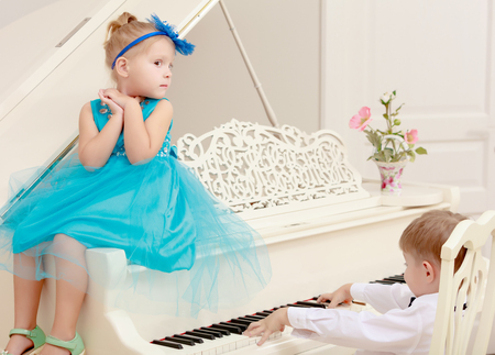 shool: Funny kids posing near the old white Grand piano. The boy presses the button , and the girl helps him.