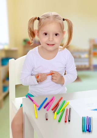 peers: Pretty little blonde girl drawing with markers at the table.Girl holding in hands blue marker.The concept of pre-school education of the child among their peers . on the background of the playroom with shelves for toys. Montessori.
