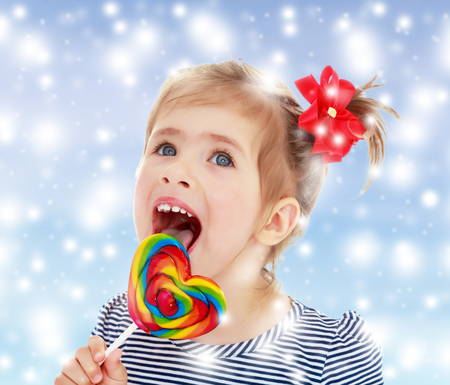 Cute little blonde girl with a red bow on her head, with pleasure licking colorful candy on a stick. Visible language which was painted in a candy color. Close-up.Gentle blue Christmas background