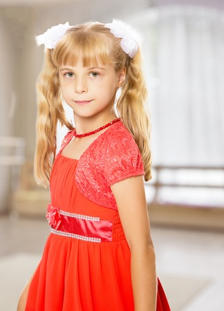 A very beautiful little girl with long, blonde ponytails on her head in a bright orange dress . close-up.In a room with a large semi-circular window. Stock Photo