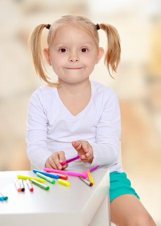 shool: Beautiful little blonde girl with white t-shirts without a pattern, draws markers at the table on a white sheet of paper. The girl is holding a pen . close-up.