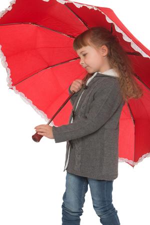 umbrela: Beautiful little girl in autumn clothes under the red umbrella close-up