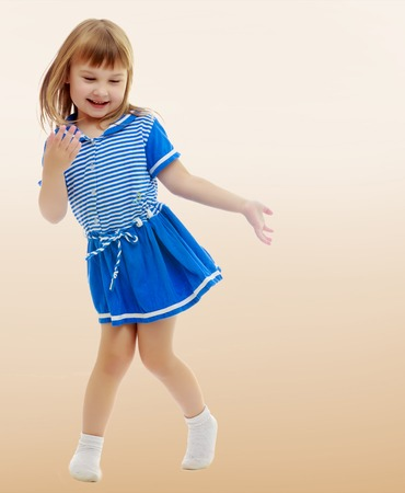 On a brown background a smooth transition from dark to light. Gentle little girl in a short blue dress similar to a sailor suit, with pleasure poses for the camera. Stock Photo
