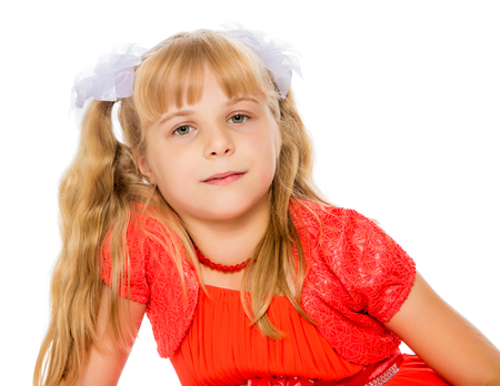 ponytails: A very beautiful little girl with long, blonde ponytails on her head in a bright orange dress . close-up-Isolated on white background