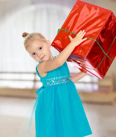 Caucasian little girl in a blue dress, holding the hands of the big red box that is a gift.The girl lifted the box over his head.