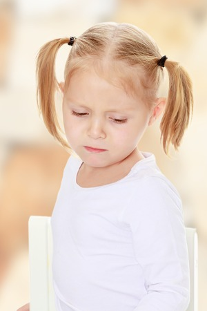 shool: Beautiful little blonde girl with pigtails on his head, white t-shirts without a pattern. The girl is upset about something. Close-up.