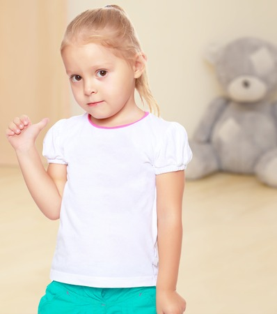 shool: Cute little blond girl in white tank top without a pattern.Girl shows thumb to the side.The concept of preschool development of the child ,against a childs room where in the background a Teddy bear Stock Photo