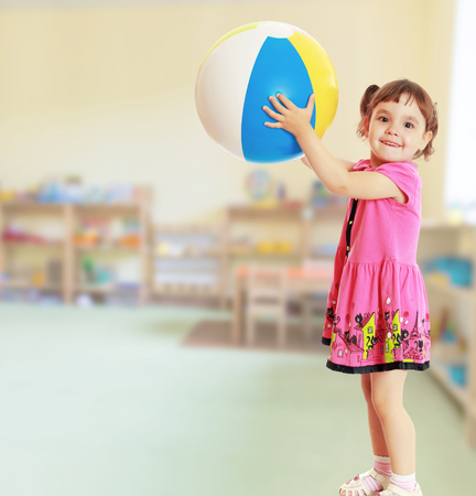 Happy little girl with pigtails on the head , in a pink dress. The girl lifted a large, inflatable striped ball.On blurred background the great hall of the kindergarten