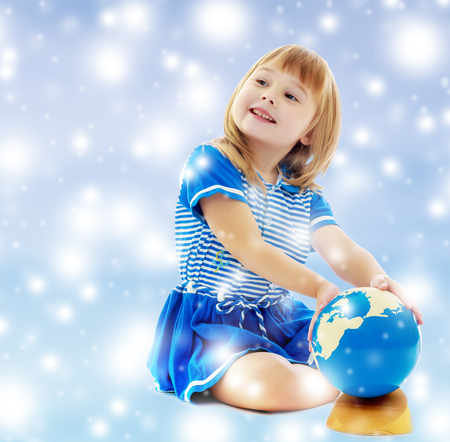 On a blue background with white blurry circles, like Christmas snowflakes. Nice little girl in a Sea blue dress sitting on the floor. Girl turns hand the globe. Stock Photo