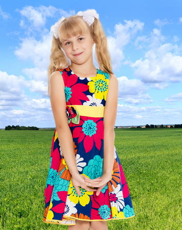 ponytails: Beautiful little girl with long blonde ponytails on her head tied with white bows, bright summer dress and knee socks Stock Photo