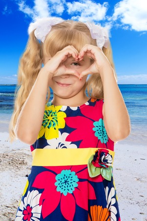 Beautiful little girl with long blond hair braided in ponytails , folded palms heart.On the background of sea beach, warm sea and blue sky with clouds. Stock Photo